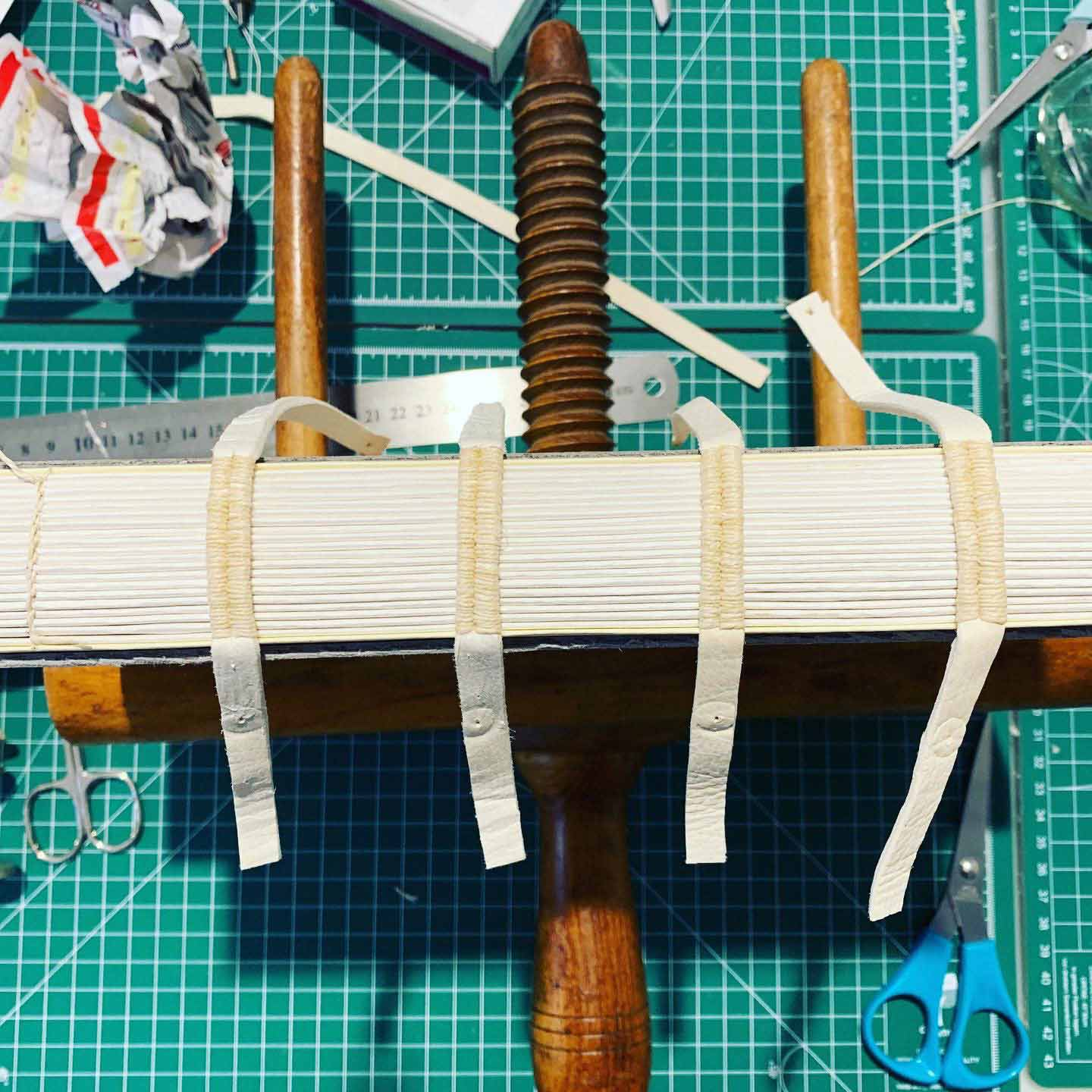 Students practicing book-making with split-thong supports made of alum-tawed leather